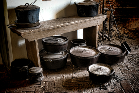 Vintage collection of old heavy duty cast iron pots and pans on an antique brick floor with scattered cooking ash from a massive fireplace in the traditional kitchen of a historic home