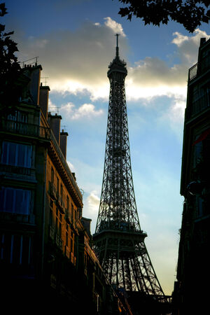 The Eiffel Tower famous landmark rising above classic Parisian residential buildings in a fashionable neighborhood street in late afternoon in Paris France