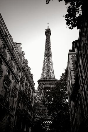 The Eiffel Tower landmark at the end of a quiet residential neighborhood Parisian street with old French city buildings in Paris France in nostalgic black and white