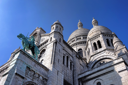 Sacre Coeur Basilica of the Sacred Heart landmark exterior architecture detail of dome and towers built of travertine in Romano Byzantine architectural style with famous bronze equestrian statue of Saint Joan of Arc on Butte Montmartre in Paris France Editorial