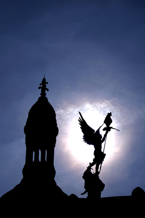 Saint Michael the Archangel statue and church cupola on the roof of the Sacre Coeur Basilica of the Sacred Heart tourism landmark and Roman Catholic shrine on Butte Montmartre backlit by the sun in Paris France