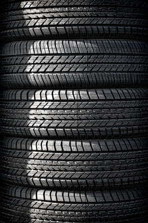 car shop: Stack tower of new passenger automobile car tires with all weather thread in a vertical pile for display and sale at an auto wheel repair shop Stock Photo
