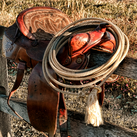American West Legend rodeo cowboy roping lariat lasso hanging on the horn of an authentic leather western saddle resting on a wood fence post