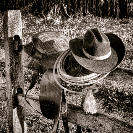 legend: American West Legend rodeo cowboy hat and roping lariat lasso atop an authentic weathered leather western saddle on a wood fence post at a frontier ranch