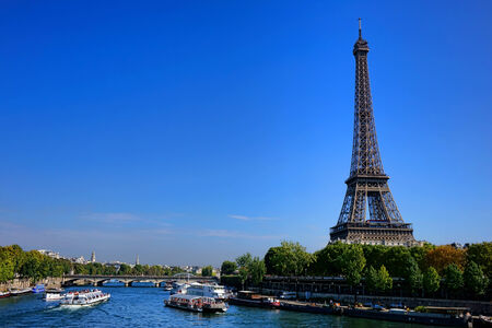 Sightseeing tourist and city visitor boats in busy traffic jam on the Seine River under the famous Eiffel Tower Parisian landmark in Paris France Imagens