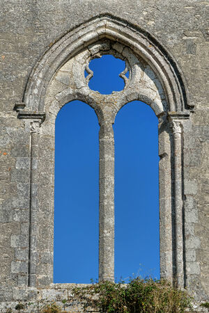 church window: Old gothic ruin church nave window empty frame over open blue sky in an abandoned ruined abbey Stock Photo