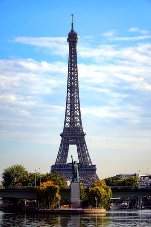 ile de france: Statue of Liberty replica on Ile aux Cygnes at Pont de Grenelles bridge over the Seine River in front of the Eiffel Tower landmark monument in Paris France