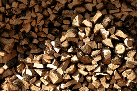 Stack pile of wood burning fire logs cut from old trees for firewood heating fuel