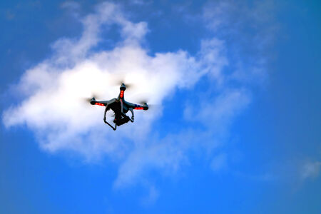 appearing: Flying remote unmanned robotic aircraft drone appearing above in flight out of a cloud over clear blue sky for possible video surveillance and aerial photography or simply just a toy Stock Photo
