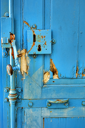 door knob: Old door lock with vintage locking handle with wood knob on an antique blue wooden doorway entrance with wear and tear usage damage and peeled paint on a historic home Stock Photo
