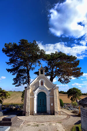 religious service: Small chapel for religious service and funeral mass flanked by shade trees in an old rural cemetery in the countryside of France
