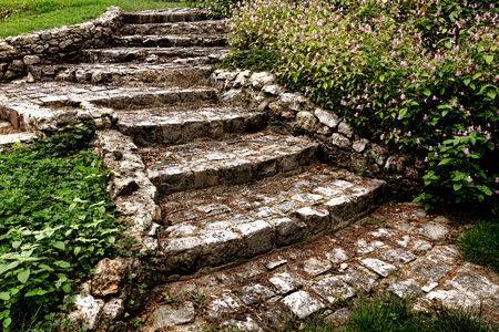 Antique cobblestone stairway with old and worn Belgian pavers stone block stairs steps and ancient rock wall stringer in an old decorative ornamental landscape garden