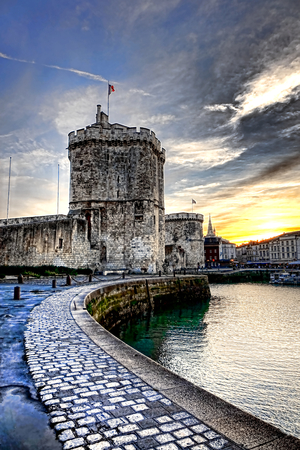 Tour de la Chaine medieval fortress tower and stone pier over the harbor water at sunset at the fortified entrance of the old port of La Rochelle in the French city in France Editorial