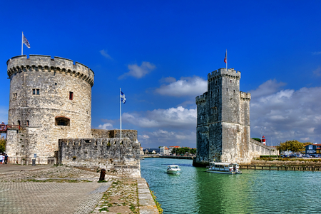 Tour de la Chaine and Saint Nicolas medieval fortress towers and stone pier over the harbor water as fortified entrance to the old port of La Rochelle with tourism boats in the French touristic city in France