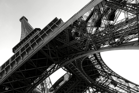 The Eiffel Tower landmark steel structure and pylon leg detail with iron beams assembly up perspective view from bellow in Paris France in classic black and white