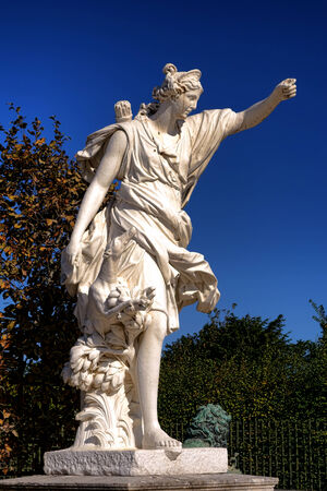 Roman goddess Diana the huntress marble hunting statue with hunt dog in the palace of Versailles Gardens in France Editorial