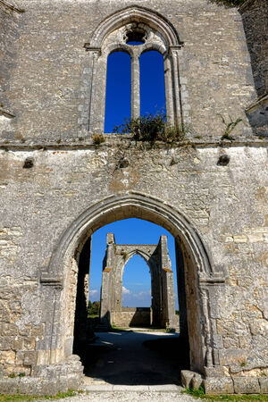 abbaye: Gothic empty window and open stone wall arches at the abandoned medieval ruins of the Abbaye Notre Dame or Chateliers abbey monument on Ile de Re in France Stock Photo