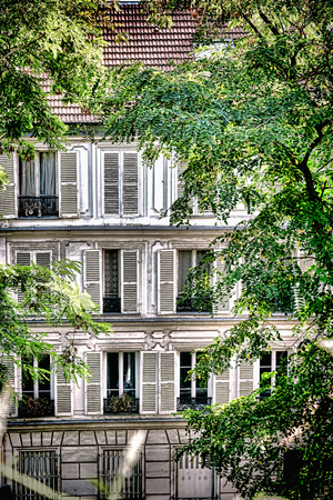 Old Parisian residential apartment building with antique wood shutters and vintage casement windows behind mature trees on a quiet street in a traditional neighborhood in Paris France