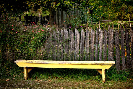 garden fence: Old yellow antique bench in historic colonial village garden with vintage wood post fence around a vegetable patch and heirloom flower shrubs