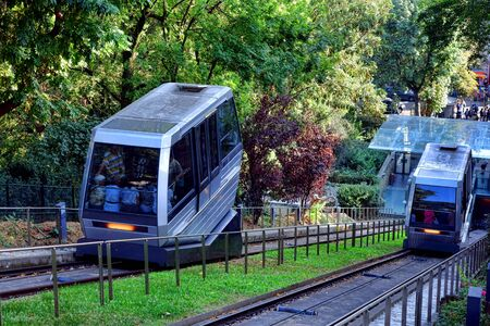 Paris attraction transportation funicular inclined railway riding up and down the Butte Montmartre below the Sacre Coeur basilica landmark and hauling visitors and Parisians to the French tourist monument Editorial