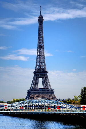 Regional SNCF French commuter train crossing the Pont Rouelle bridge over the Seine River near the famous Eiffel Tower steel landmark in Paris France