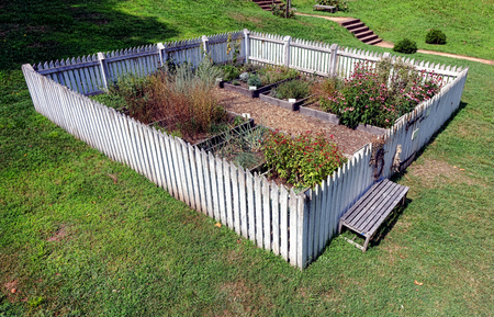 garden fence: Antique colonial garden with old fashioned white picket fence and raised plant beds for vegetable and spice growing at Hopewell Furnace National Historic Site in Pennsylvania