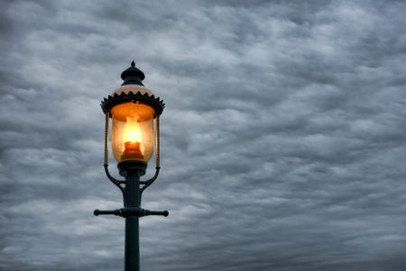 lampposts: Vintage Victorian style streetlight lamppost with warm light glow shining in a street over dramatic cloudy evening sky at dusk