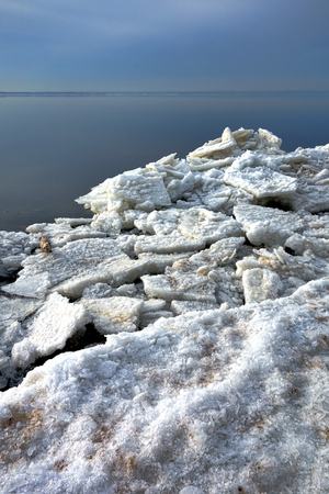 Ice float chunks and frozen icy pieces with snow on freezing shore over open bay river water in cold winter
