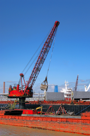 fluvial: Harbor dock industrial crane with bulk scoop loading a maritime and fluvial transportation barge in a busy coastal port Stock Photo
