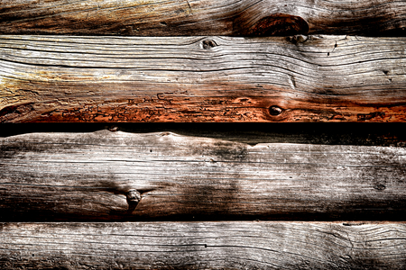 Old and weathered wood tree trunks as antique construction material on a rustic log cabin barn wall background