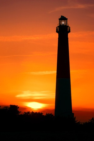 navigation aid: New Jersey coast Barnegat lighthouse aid beacon landmark tower with maritime navigation guiding light on the Atlantic shore scenic seashore at sunset over colorful nightfall sundown sky Stock Photo