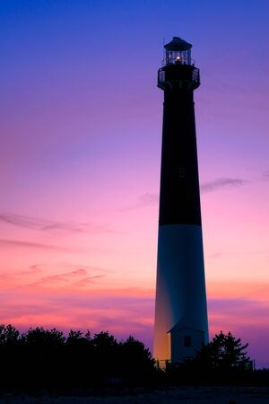navigation aid: New Jersey shore Barnegat lighthouse maritime navigation aid beacon landmark tower with guiding light on the Atlantic coast scenic seashore at dusk over colorful evening nightfall sky Stock Photo