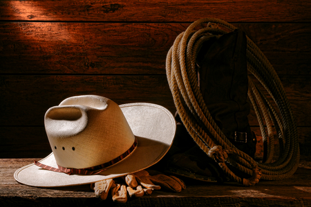 barnwood: American West rodeo cowboy authentic white straw hat and traditional rancher gloves with lariat lasso on vintage roper western boots on aged weathered barnwood floor in an old ranch barn