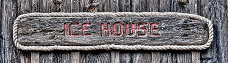 recessed: Antique ice house storage shed sign banner with red carved recessed letters on vintage weathered wood board in an antique fishing village