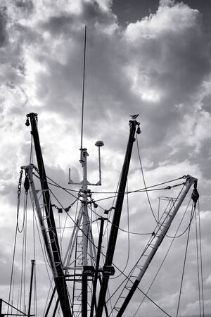 fishing fleet: Menacing storm clouds sky over docked and lined up fishing boat vessel fleet silhouetted masts and trawling net towing boom outriggers