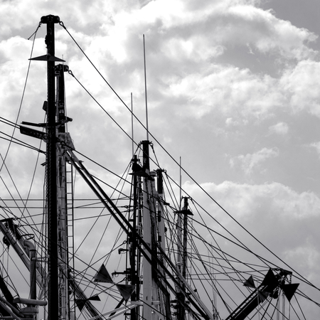 fishing fleet: Commercial fishing boats docked fleet silhouette mast and antennas with cables and wires against cloudy sky in port
