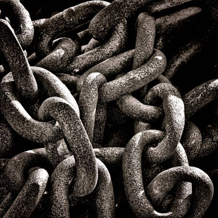 Heavy duty industrial strength corroded and rusty old maritime chain rings link in a discarded pile on a naval dock grunge background