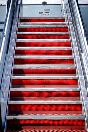 aluminum airplane: Plane passenger boarding air stairs mobile stairway ramp with red rubber riser on aluminum steps climbing to an aircraft door entrance for loading travelers access Stock Photo