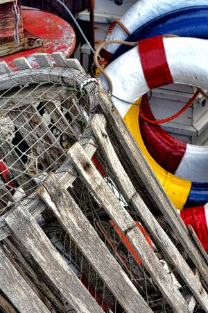 lobster pot: Antique wood lobster trap pot and vintage colors ship life preserver lifebuoys on an old fishing boat