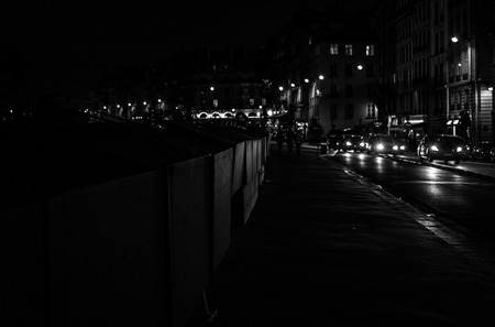 nostalgy: Cars and sidewalk at night in Paris (Quais de Seine). Bouquinistes are seen on the left Stock Photo