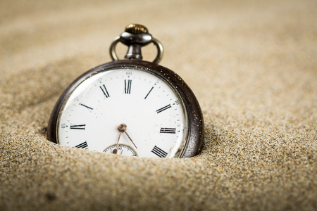 Close-up on an old pocket watch on sand
