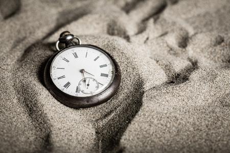 An old pocket watch on sand