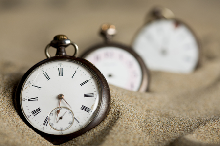 Three old gusset watches lined up in the sand Stock Photo