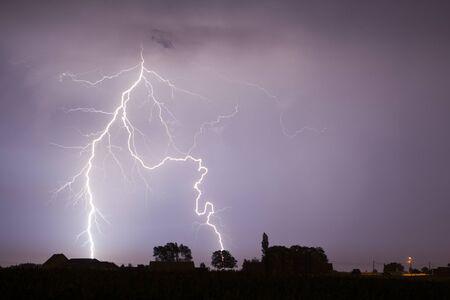 El rayo es una descarga electrostática que ocurre naturalmente durante la cual dos regiones cargadas eléctricamente en la atmósfera o el suelo se igualan temporalmente. Foto de archivo