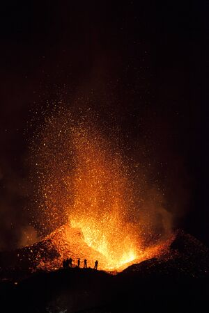 People watching Lava Fountains and Explosions of Molten Fire during the Eruption of the Eyjafjallajokull Volcano on Iceland. Foto de archivo