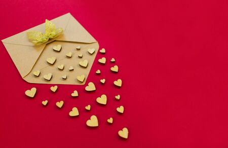 Small wooden hearts fly out of the envelope against a red background. Valentines Day. Love concept. Gift, message for lover. Copy space.