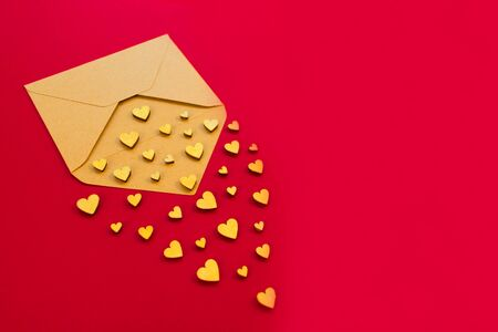 Small wooden hearts fly out of the envelope against a red background. Valentine's Day. Love concept. Gift, message for lover. Copy space. Stock Photo