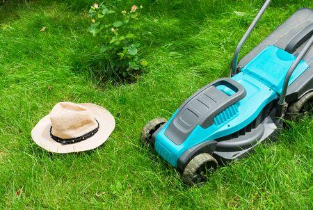 Lawn mower mowing green grass and a sunhat. Summer work in the garden. Imagens
