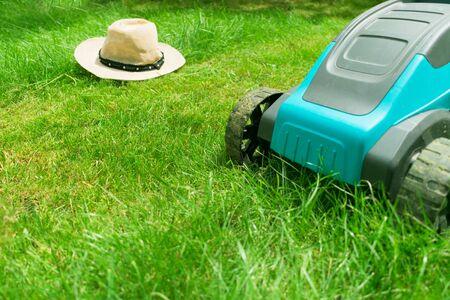 Falciatrice da giardino che falcia l'erba verde e un cappello da sole. Lavoro estivo in giardino. Archivio Fotografico