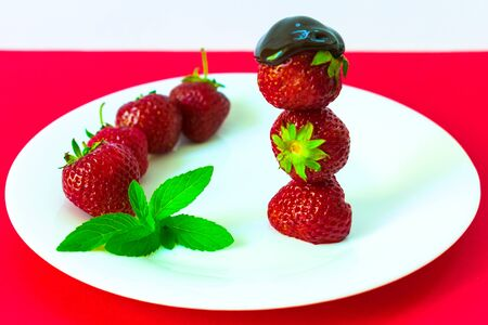 Strawberries in chocolate and mint leaves on a white plate. Red background